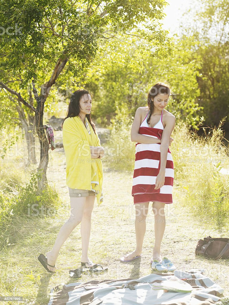 Two woman standing on riverbank wrapped in towels foto stock royalty-free