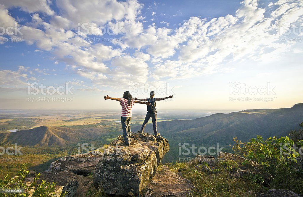 Two woman standing over mountain ridge. Freedom concept stock photo