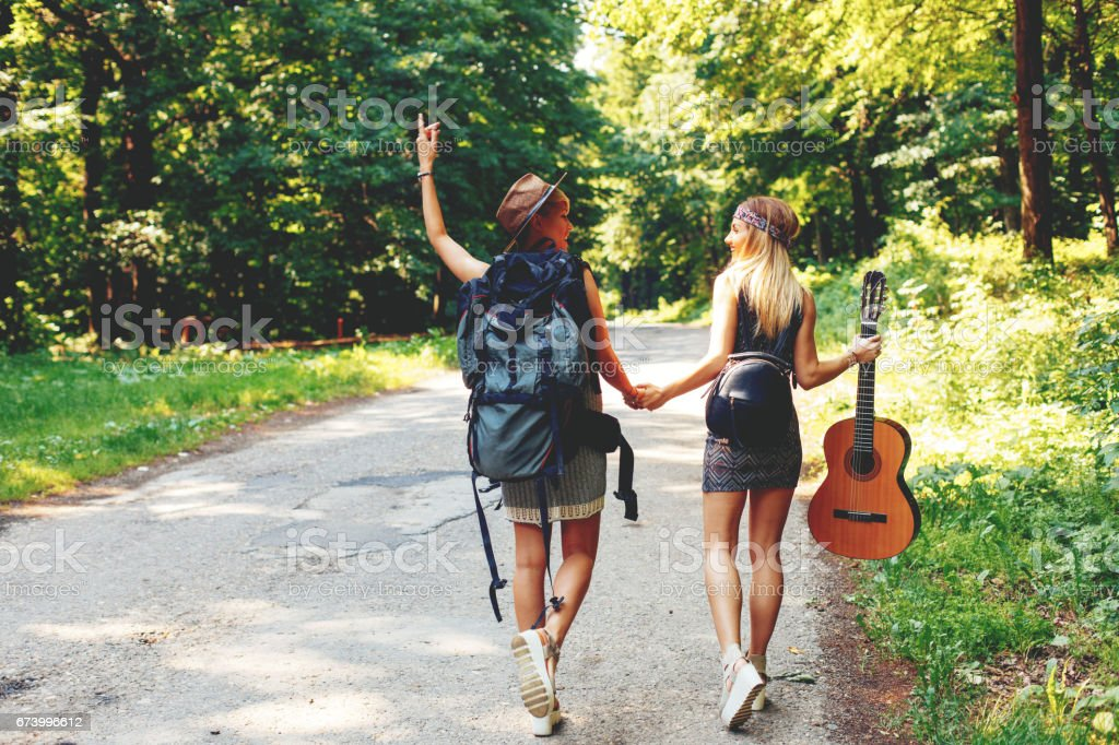 Two woman traveler walking along the road through woods royalty-free stock photo