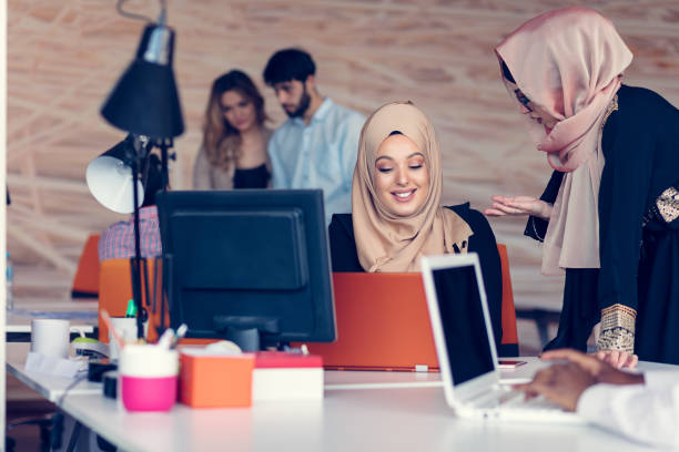 two woman with hijab working on laptop in office. - saudi woman stock photos and pictures