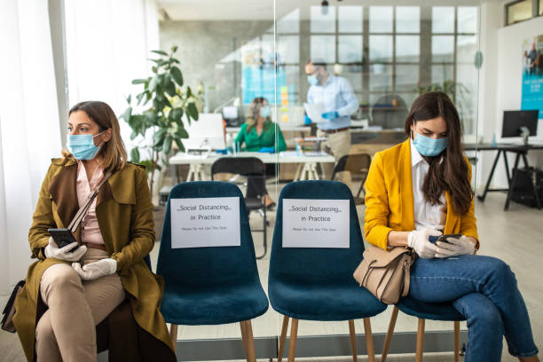 two woman with protective face mask and surgical gloves in bank waiting room - social distancing stock pictures, royalty-free photos & images
