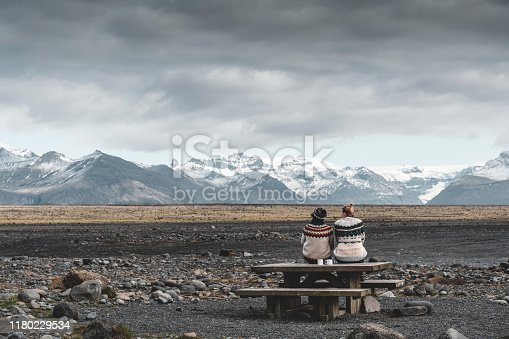 Two girls sit on a bench and admire the Icelandic landscape.