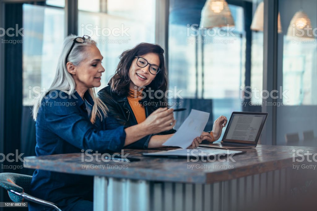 Two women analyzing documents at office stock photo