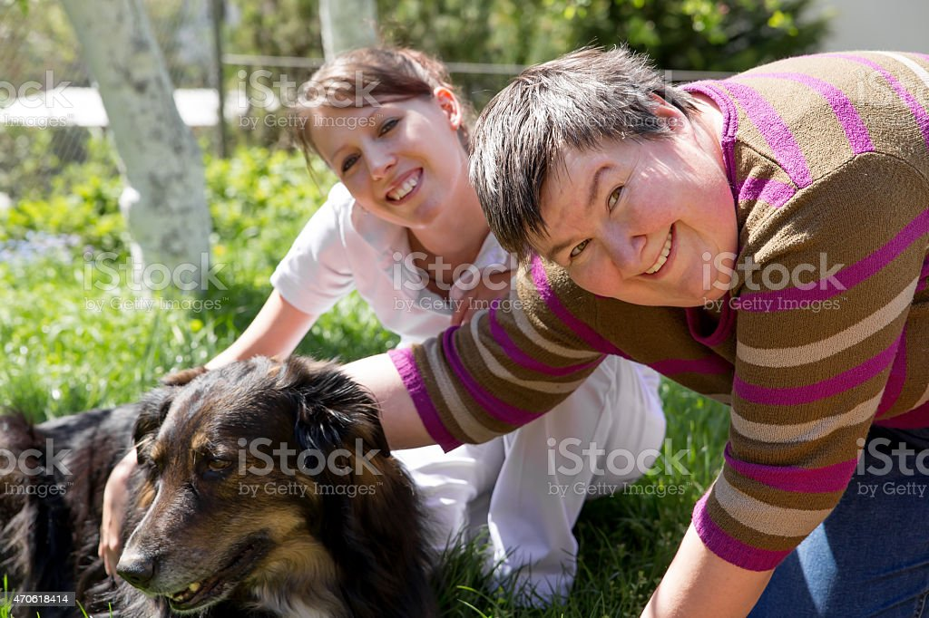 two women and a half breed dog stock photo