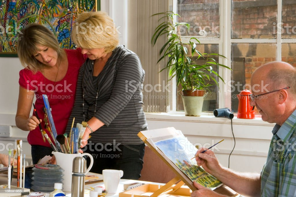 Two women and a man in art class stock photo