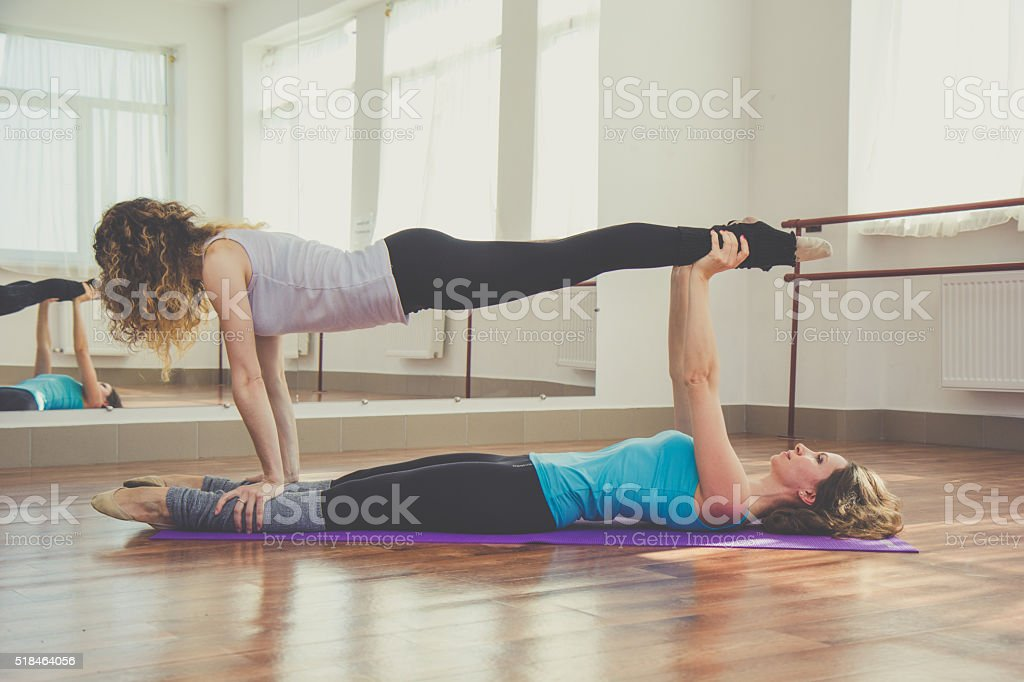 Two women are doing yoga indoors stock photo