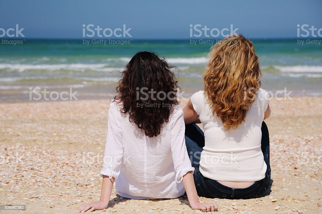 Two women are sitting on the beach stock photo