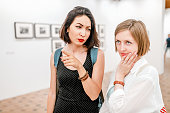 Two women art critics discuss a picture or photo in the art gallery