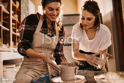 istock Two women at a pottery workshop making clay pots 894870474