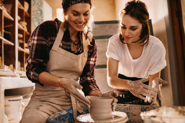 two women at a pottery workshop making clay pots - garncarz zdjęcia i obrazy z banku zdjęć