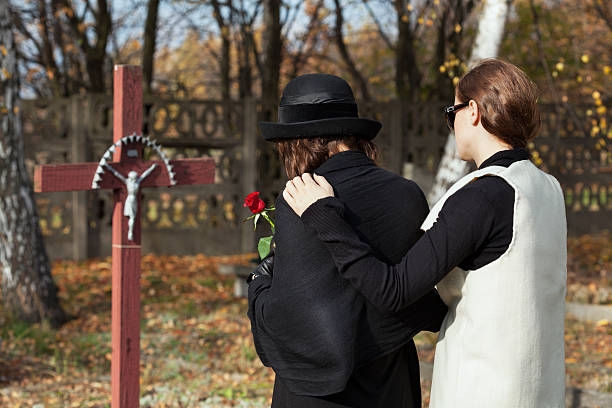 two women at cemetery in fall - funeral crying stockfoto's en -beelden