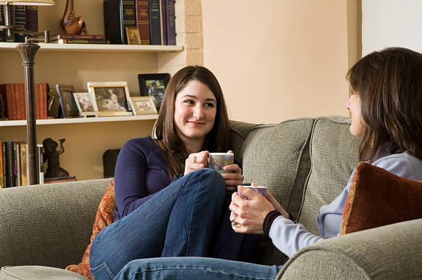 Two Women at Home Talking Over Coffee stock photo