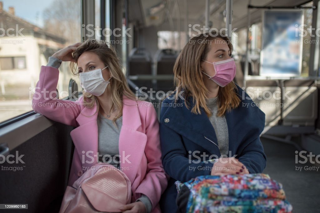 Twee vrouwen bij openbaar vervoer tijdens virusepidemie - Royalty-free 2020 Stockfoto