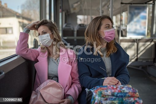 Two young women at public transport during virus epidemic. Two women sitting at public transport wearing pollution masks.