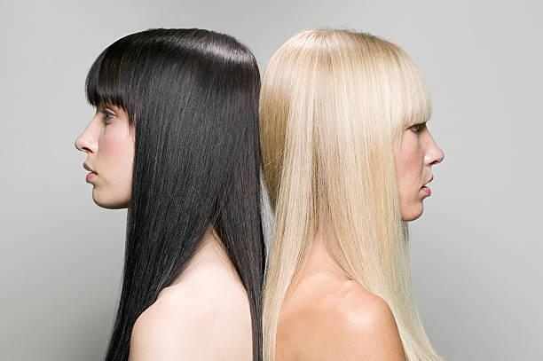 zwei frauen rücken an rücken - haarfarbe ohne ammoniak stock-fotos und bilder