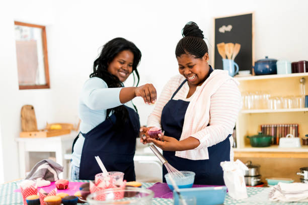 Two women baking baking together and decorating cupcakes stock photo