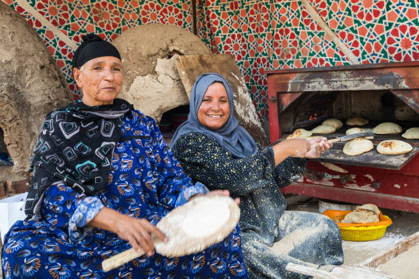 Two women baking traditonal Al-Shamsi bread in wood-fired clay oven stock photo