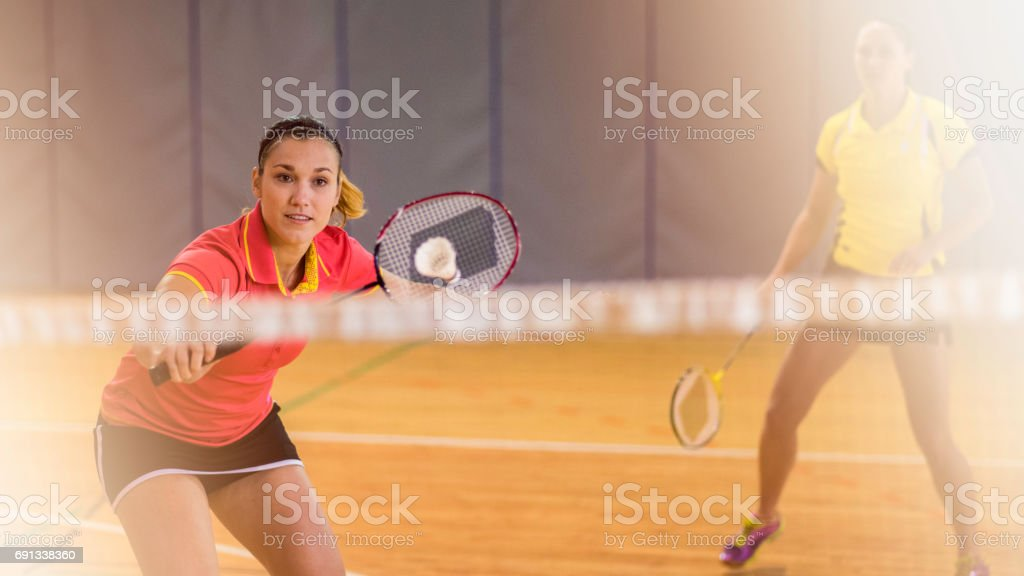 Two women behind the net playing badminton stock photo