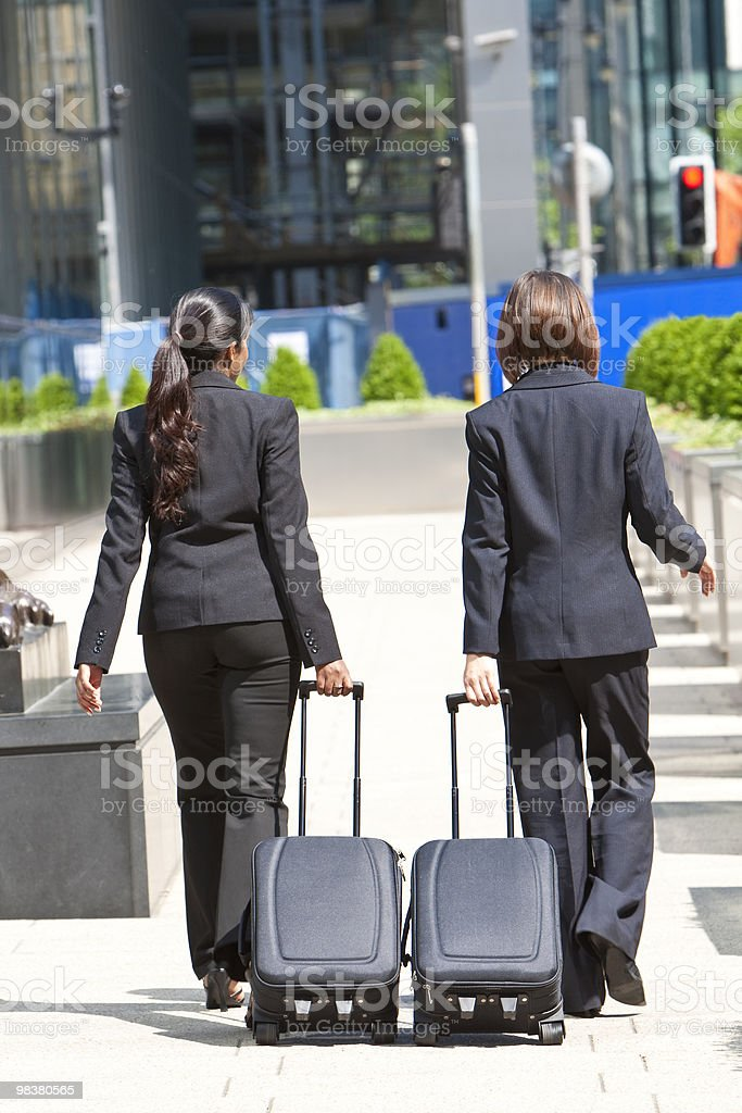 Two Women Business Travellers Walking With Rolling Suitcases royalty-free stock photo