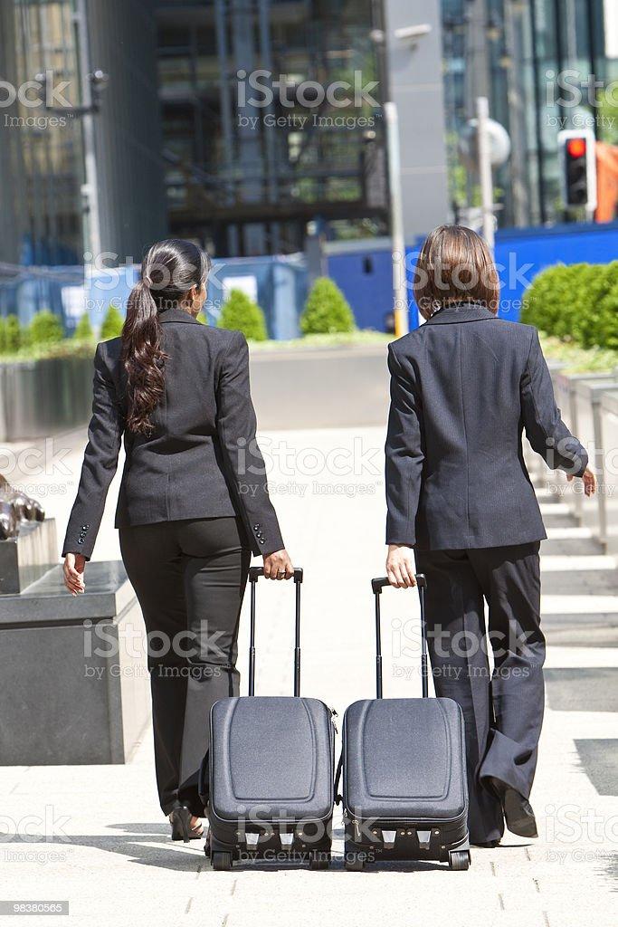 Due donne uomini d'affari a piedi con dolci le valigie foto stock royalty-free