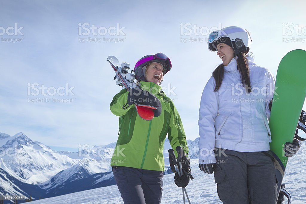 Two women carrying skis and snowboard. royalty-free stock photo