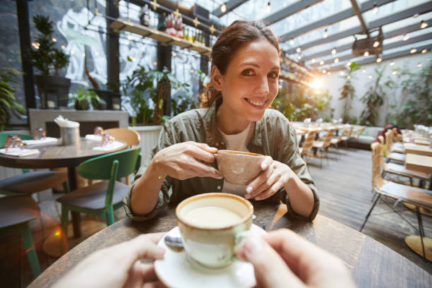 Two Women Chattering over Coffee Fisheye view of smiling woman holding coffee cup talking to friend across table in cafe, POV personal perspective stock pictures, royalty-free photos & images