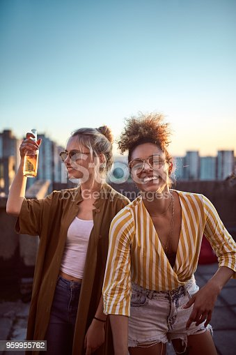 istock Two women cheering at roof party. 959955762