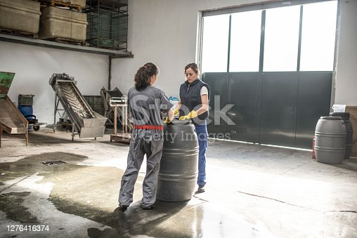 Two women cleaning and exams a barrel in factory warehouse