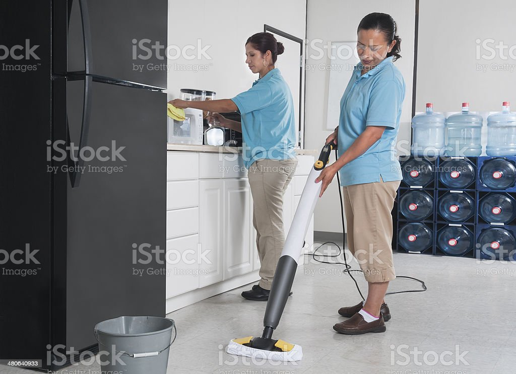 Two Women Cleaning a Corporate Break Room royalty-free stock photo