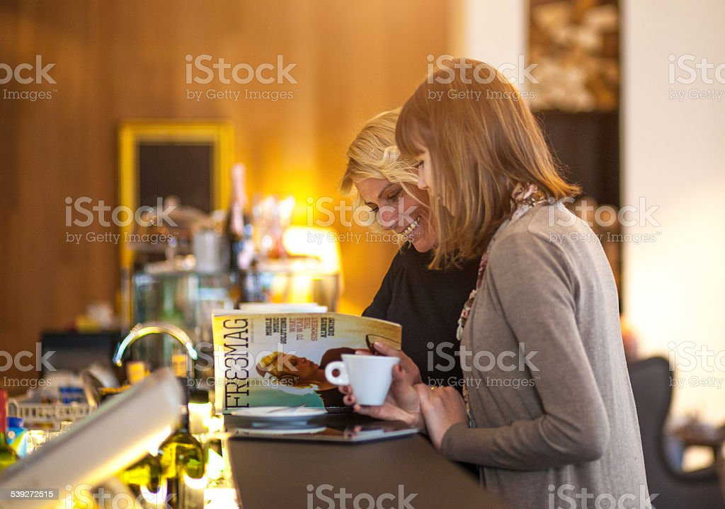 Two women coffee shop reading magazine stock photo