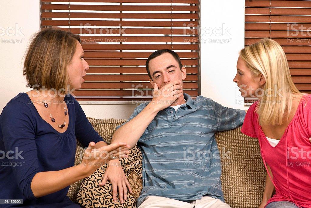 Two women confront their cheating boyfriend stock photo