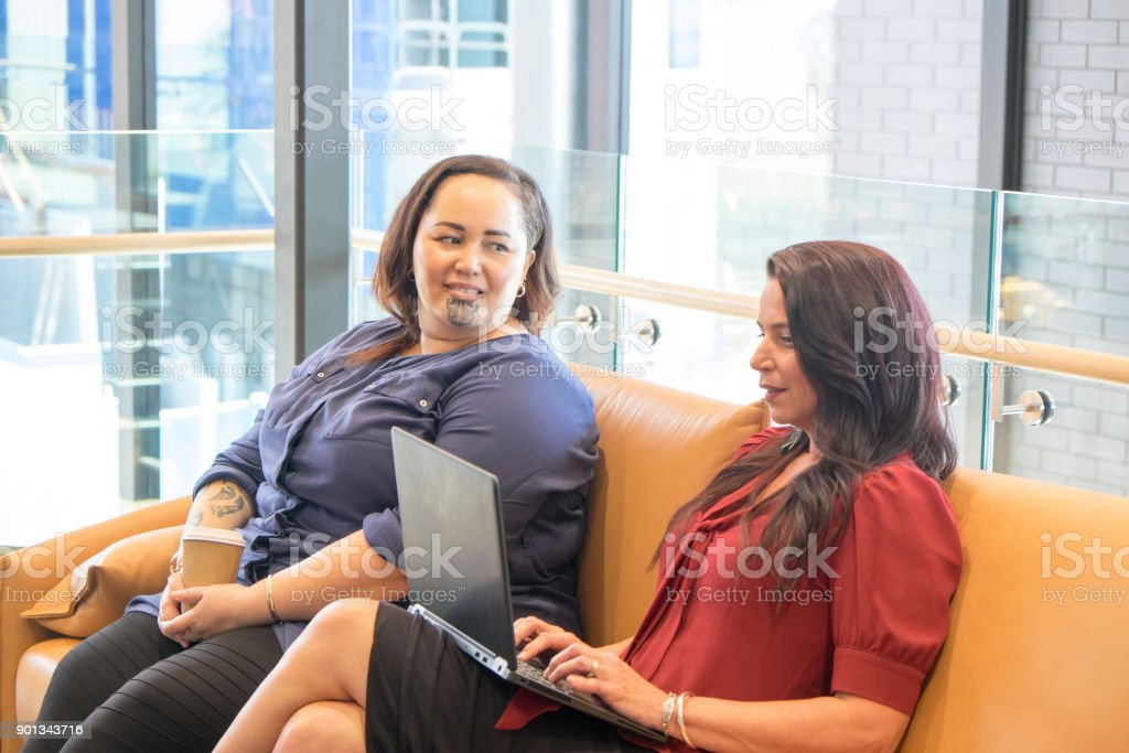 Two women co-workers brainstorming a project; caucasian female is working on laptop computer; Maori employee has tattoos including facial to moko. stock photo