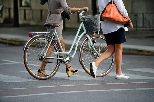 Two women crossing street with bike - foto de stock