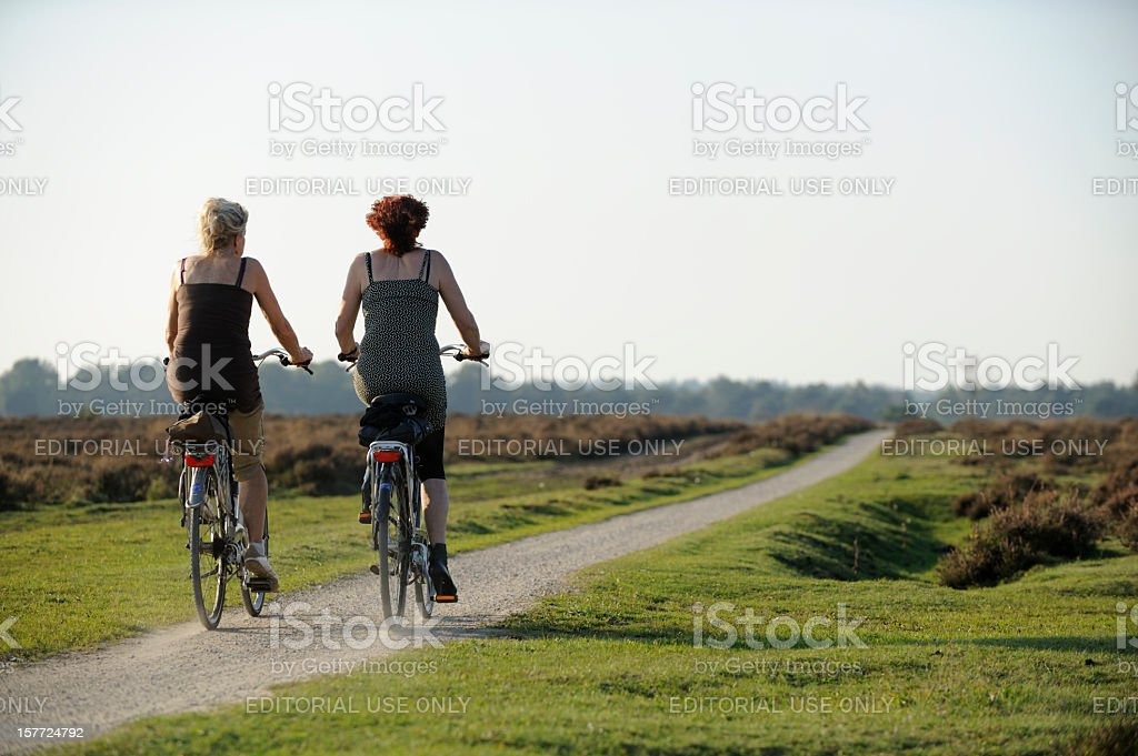 Two women cycling in nature stock photo