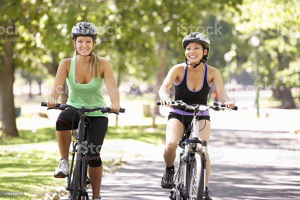 Two Women Cycling Through Park royalty-free stock photo
