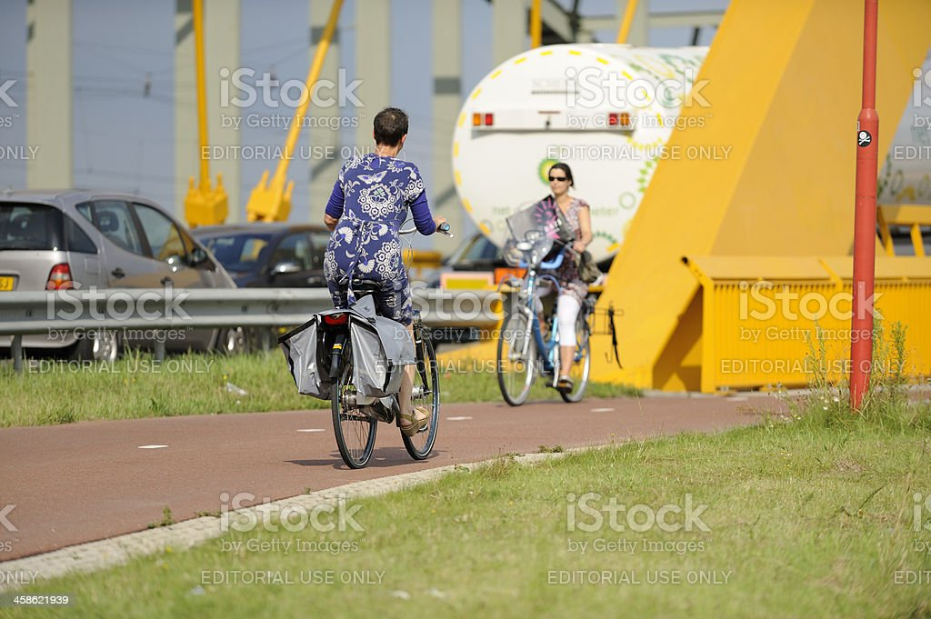 Two women cycling to and from Hogeweidebrug in Utrecht royalty-free stock photo