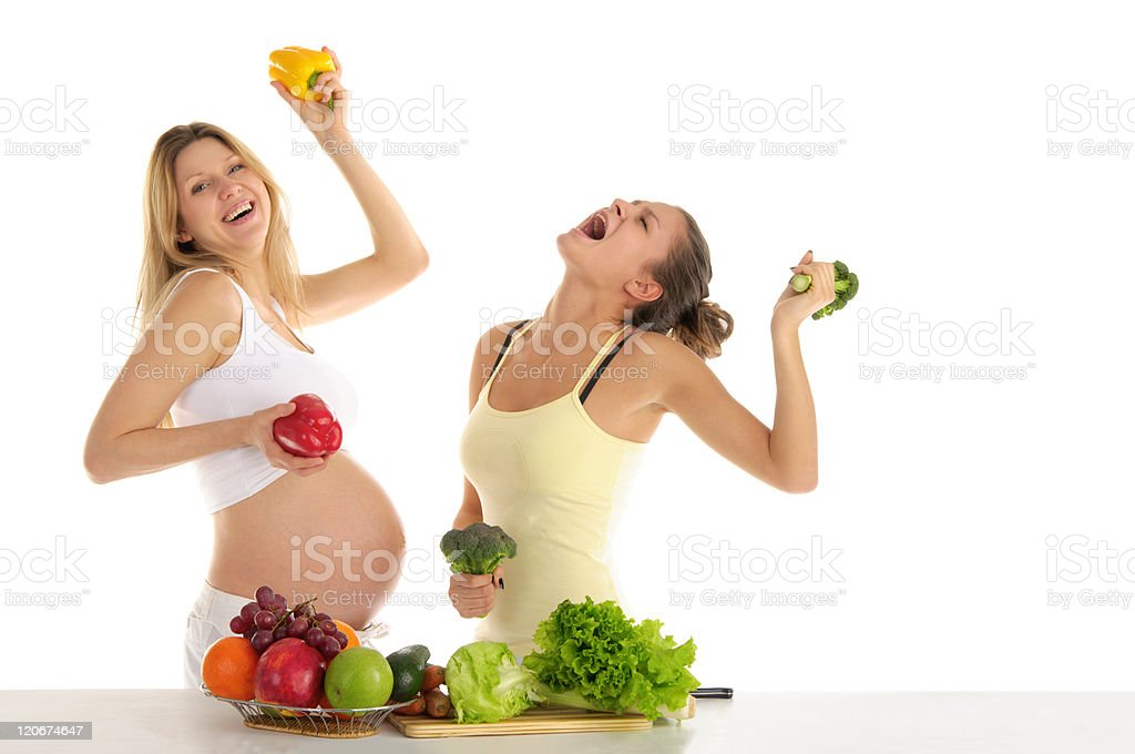 Two women dance with fruits and vegetables royalty-free stock photo