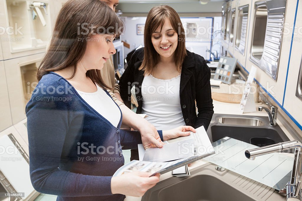 Two women discussing design options for furniture purchase stock photo