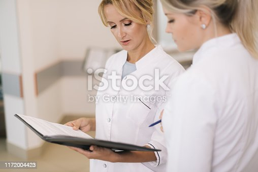 istock Two women doctors standing with clipboard at hospital and discussing cases 1172004423