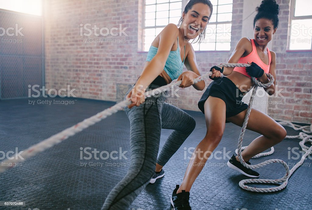 Two women doing intense workout at gym stock photo