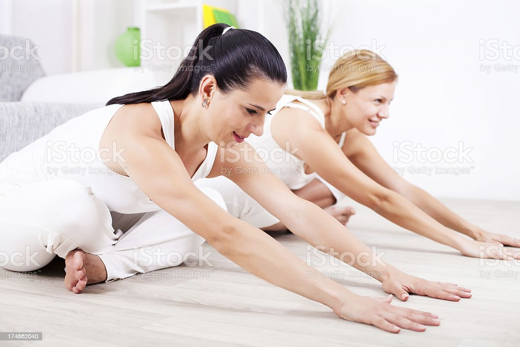 Two women doing yoga exercise at home. royalty-free stock photo