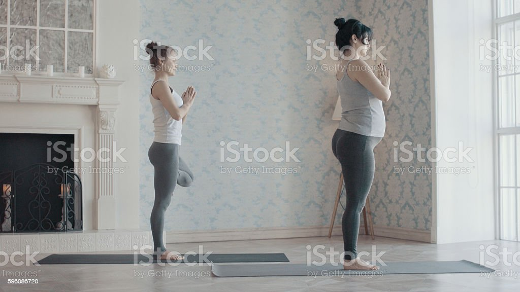 Two women doing yoga exercises royalty-free stock photo