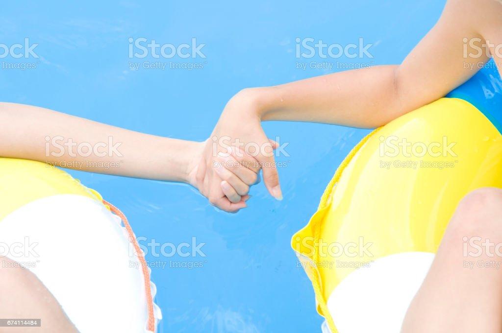 兩個女人穿著泳衣在手牽你的手 免版稅 stock photo