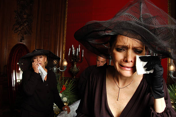 Two Women Dressed in Black and Crying at Funeral stock photo