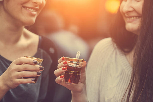 two women drinking cay, traditional turkish tea, in istanbul - turkse etniciteit stockfoto's en -beelden