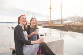 Two beautiful nordic girls at Oslo harbour enjoying life, talking and looking at smart phone, with ships on background. They also hold a cup of coffee in the hands. Lifestyle and friendship concepts.