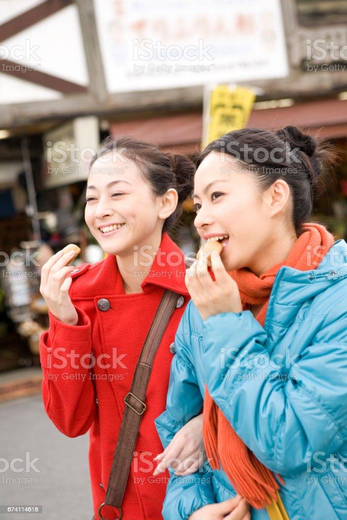 Two women eat the bun in tourist areas royalty-free stock photo