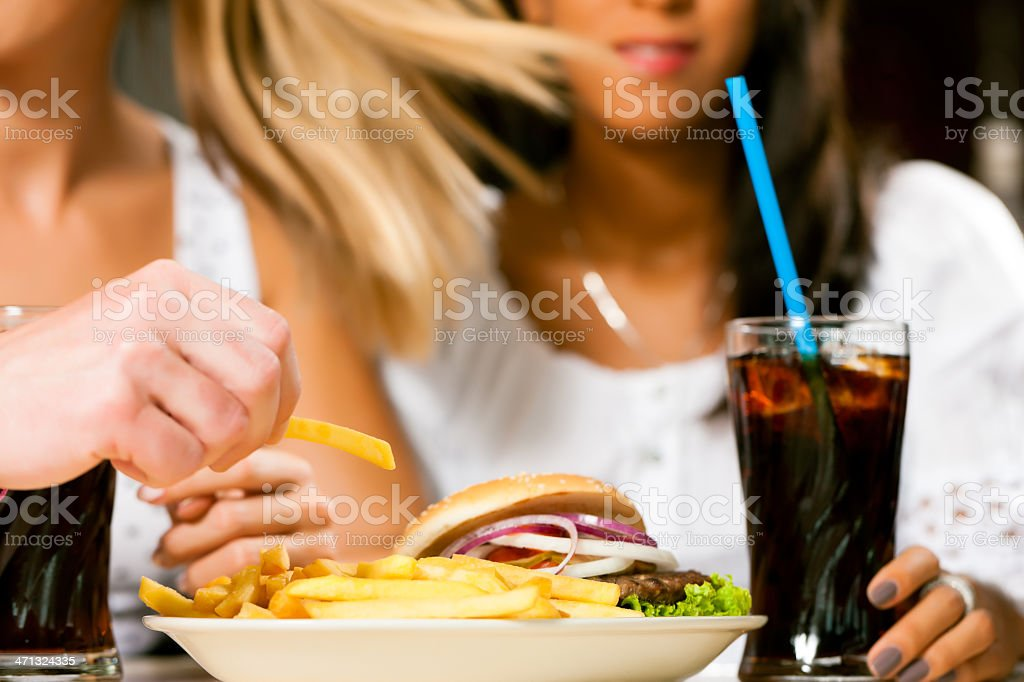 Two women eating hamburger and drinking soda royalty-free stock photo