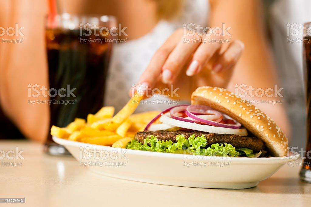 Two women eating hamburger and drinking soda royalty-free stock photo
