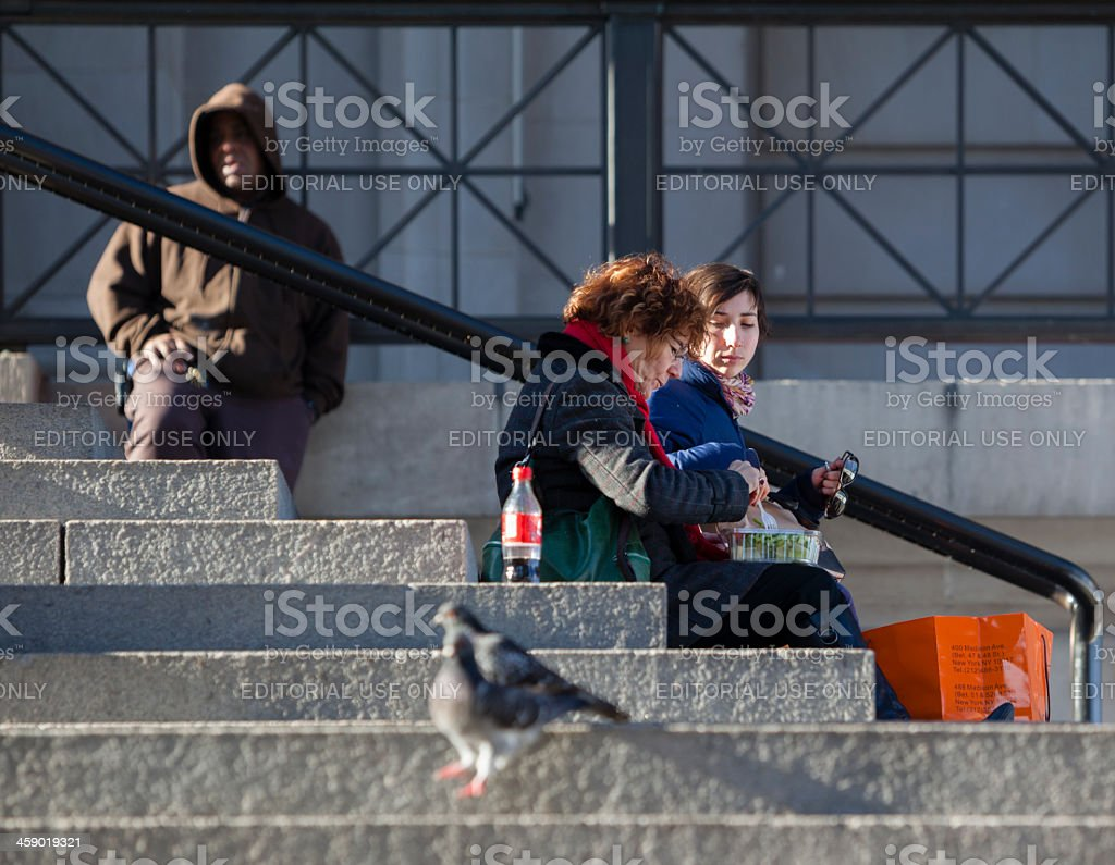 Two women eats on the stairsteps. royalty-free stock photo